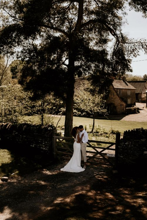 Black Bride in Lace Wedding Dress and Groom in White Shirt and Trousers Embracing in the Field