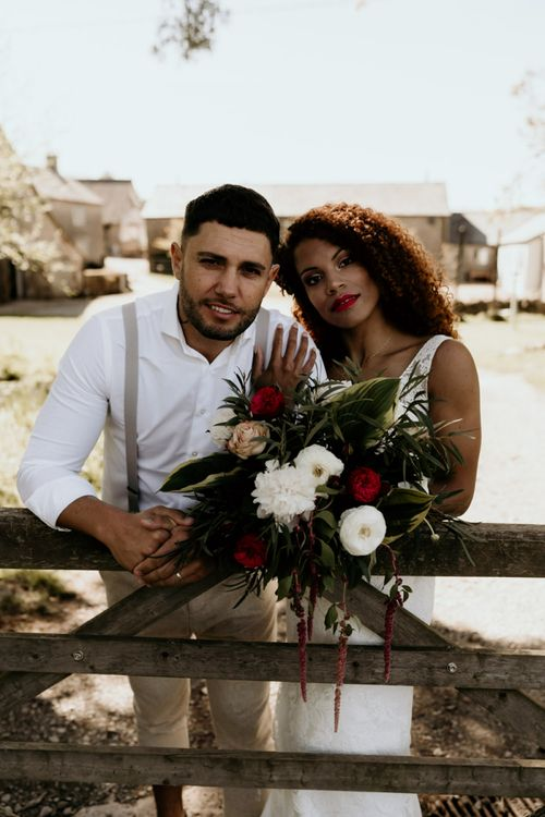 Black Bride in Lace Wedding Dress and Groom in White Shirt and Braces Embracing Next to Country Fence
