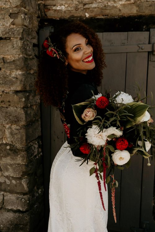 Black Bride with Afro Hair Wearing Leather Jacket Holding a Red, White and Foliage Bouquet