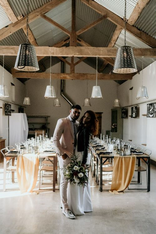 Black Bride in Lace Wedding Dress and Leather Jacket Standing Next to Groom in Blazer and Loafers