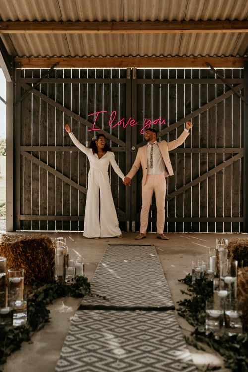 Black Bride with Afro Hair  in White Jumpsuit with Groom in Pink Suit Standing Next to Neon I Love You Sign