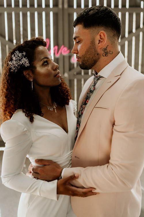 Black Bride with Afro Hair and Cheek Highlighter and Groom in Pink Blazer and Floral Tie