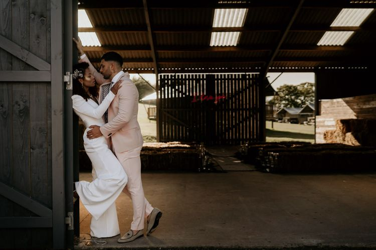 Black Bride with Afro Hair and Cheek Highlighter and Groom in Pink Suit and Floral Tie