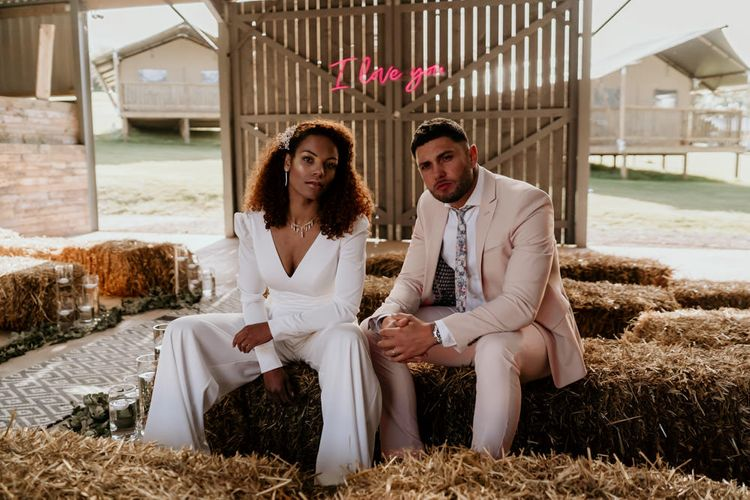 Black Bride with Afro Hair in Jumpsuit and Groom in Pink Suit Sitting On Hay Bales in a Barn