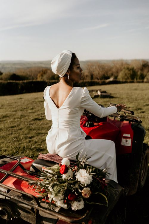 Black Bride in White Jumpsuit and Head Wrap Sitting Quad Bike
