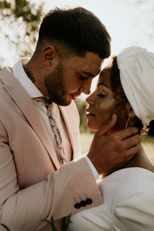 Black Bride with Head Wrap and Cheek highlighter and Groom in Pink Blazer Embracing