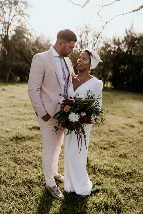 Black Bride in White Jumpsuit with Head Wrap  and Groom in Pink Suit