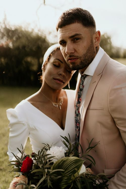 Black Bride in White Jumpsuit with Head Wrap  and Groom in Pink Blazer