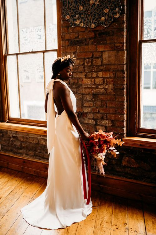 Bride holding a backless, halter neck wedding dress with caramel, raspberry and rust wedding theme bouquet