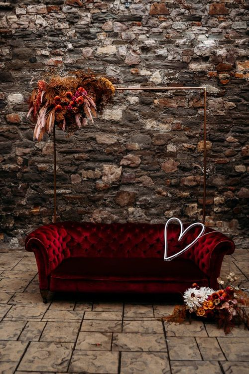 Caramel, rapsberry and rust wedding theme  seating area with velvet sofa a copper frame decorated in flowers