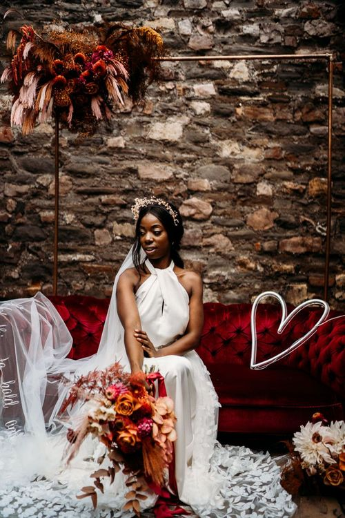 Bride sitting on a red velvet sofa in a Halfpenny London wedding dress