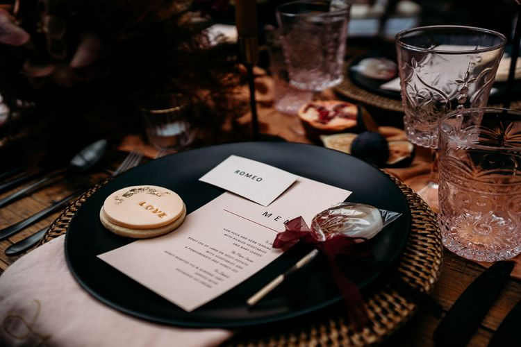 Place setting rattan mat, black plate, menu card and wedding favours