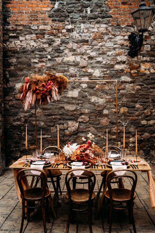 Caramel, raspberry and rust wedding theme table decor and flowers