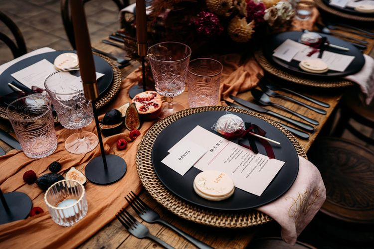 Place setting with black tableware and embroidered napkin