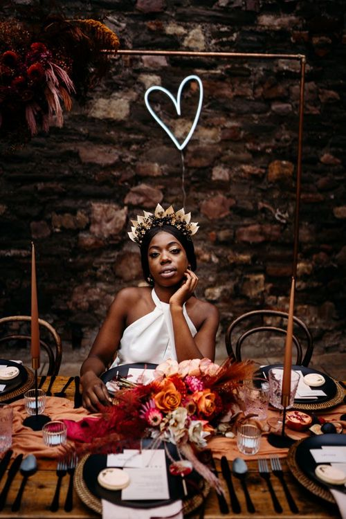 Bride sitting at a caramel, raspberry and rust wedding theme tablescape
