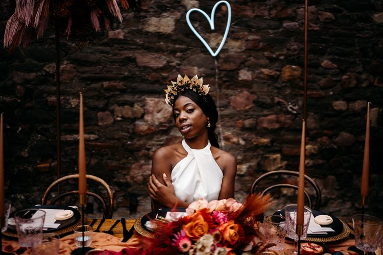 Bride sitting at a bohemian luxury tablescape with heart neon sign