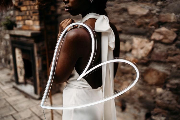 Bride holding a white neon heart on her arm for rust wedding theme