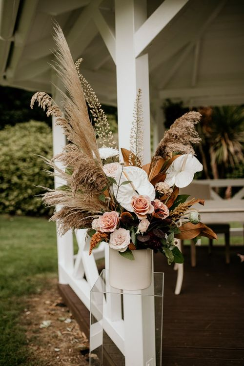 Altar floral arrangement with pampas grass, pink roses and white Anthurium flowers