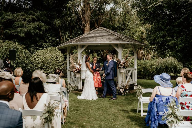 Nigerian bride and groom exchanging vows at the wooden gazebo altar