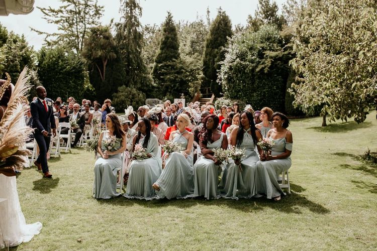 Bridal party sitting on the front row at the outdoor wedding ceremony