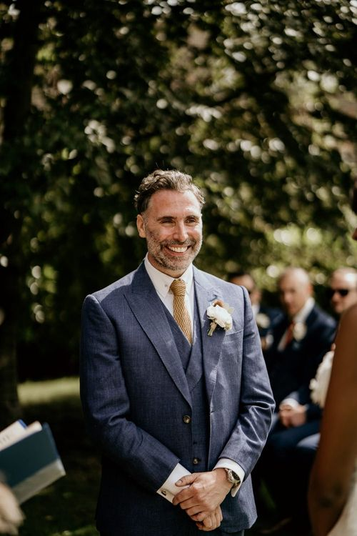 Smiling groom in navy suit standing at the altar