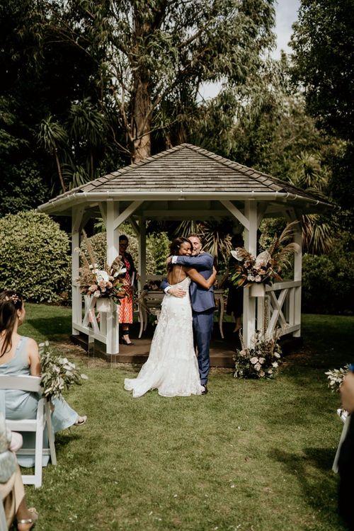 Nigerian bride and Irish Groom hugging at the outdoor wedding ceremony