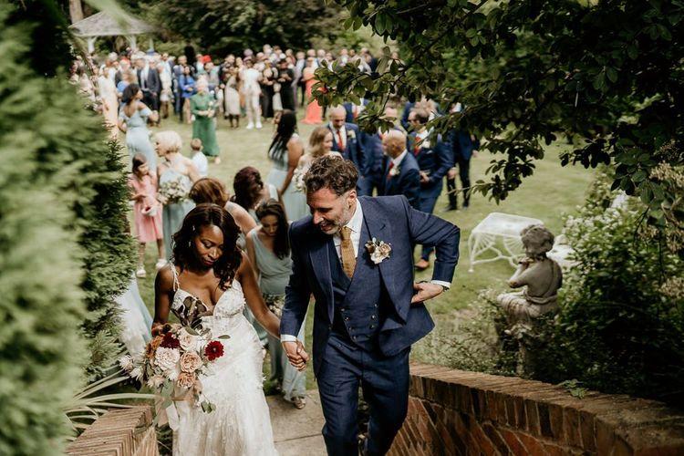 Black bride in Riki Dalal wedding dress and Irish groom in navy suit holding hands