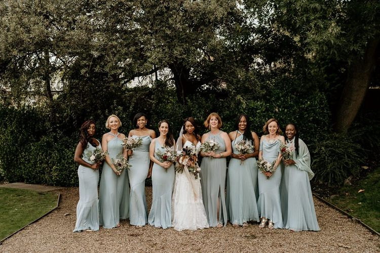 Bridal party portrait with bridesmaid in pale green dresses from Oasis