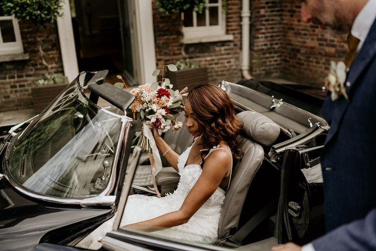 Black Bride in Riki Dalal wedding dress getting into E-Type Jaguar wedding car