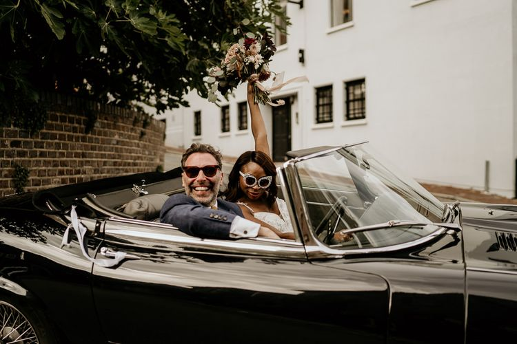 Black bride and Irish Groom in convertible wedding car