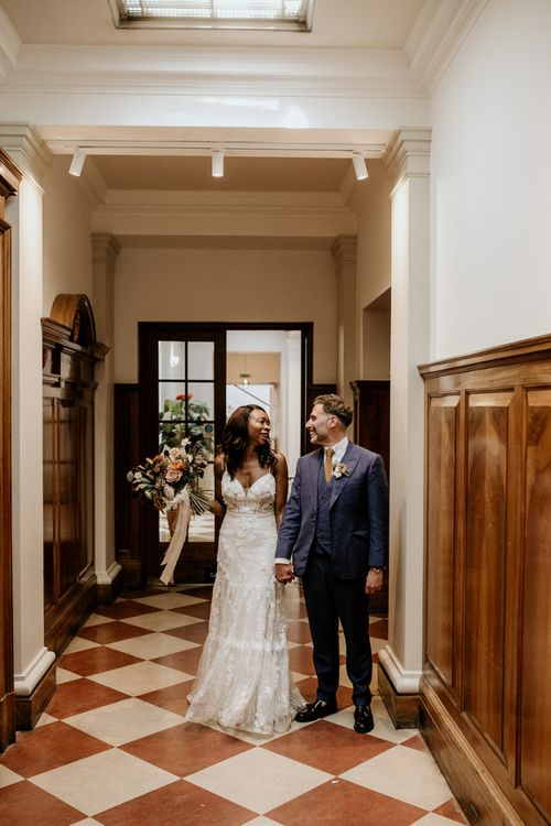 Nigerian bride in Riki Dalal wedding dress and Irish Groom holding hands
