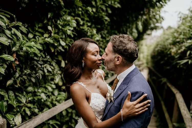 Black Bride in lace wedding dress with straps and Groom in navy suit embracing