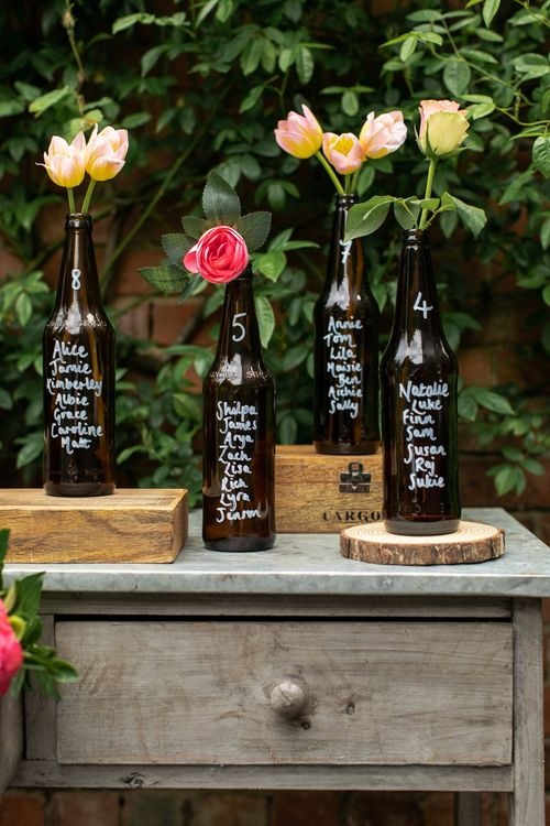 Bottle table plan for a rustic wedding, created using dark brown beer bottles, a white Pebeo pen, wooden crates and log slices, peonies and tulips.