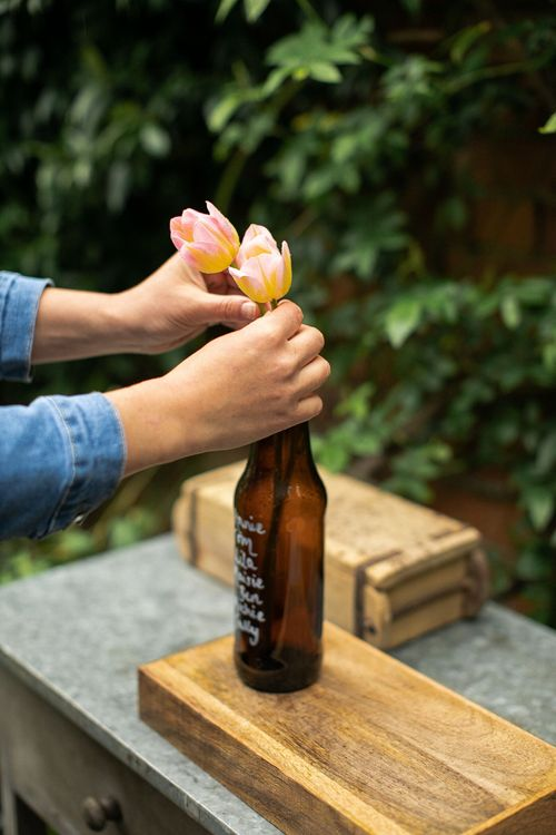 Person putting two pink and yellow tulips inside a brown beer bottle to create a wedding seating plan