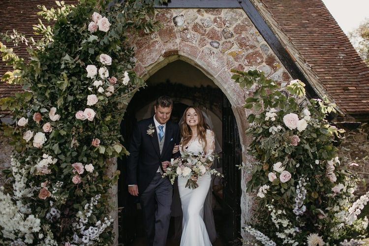 Bride in Lace St Partrick Wedding Dress and Groom in Morning Suit Exiting the Church Wedding Ceremony with Doorway Floral Arrangements