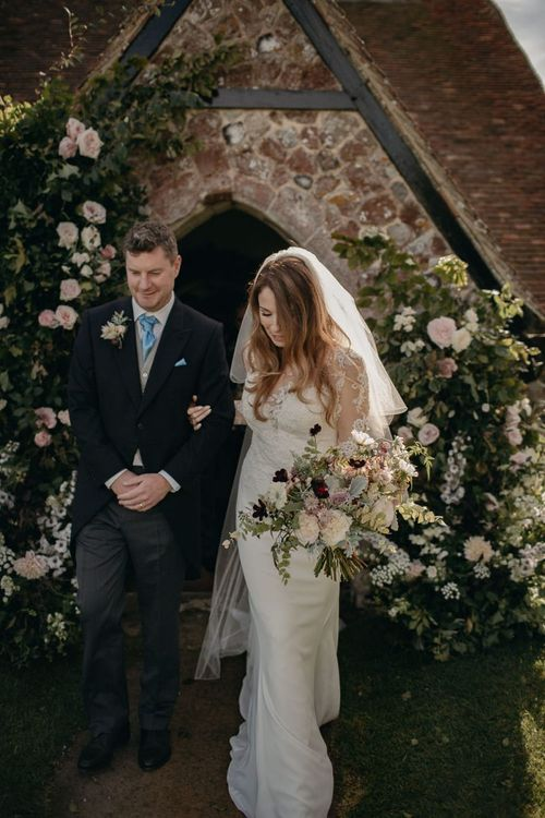 Bride in Lace St Partrick Wedding Dress and Groom in Morning Suit Exiting the Church