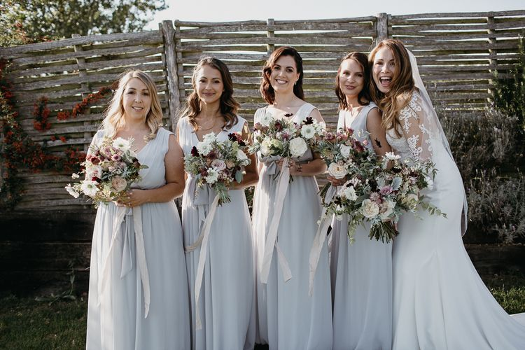 Bridal Party Portrait with Bridesmaids in Grey Dresses and Bride in Lace Wedding Dress Holding Their Widflower Bouquets