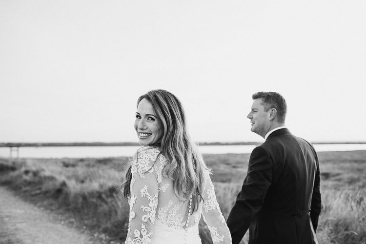 Beautiful Bride in Lace La Sposa Wedding Dress Holding Hands With Her Groom