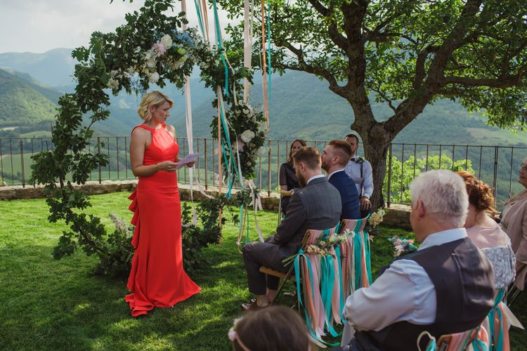 Outdoor Wedding Ceremony with Floral Moon Gate and Chair Back Ribbon Decor