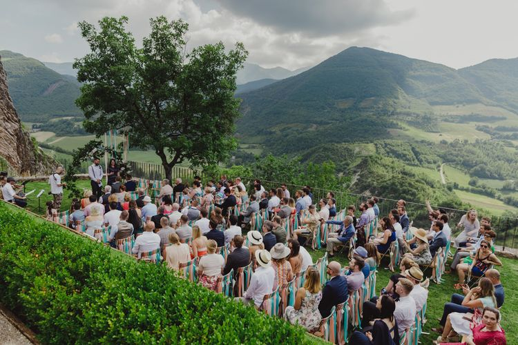 Outdoor Wedding Ceremony at Castello di Naro in Italy with Floral Moon Gate and Ribbon Chair Back Detail