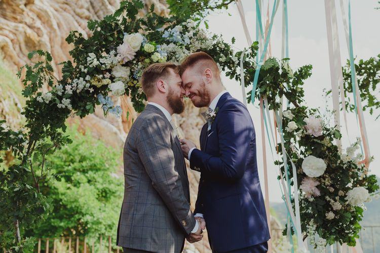 Mr & Mr Embracing in Front of Their Floral Moon Gate