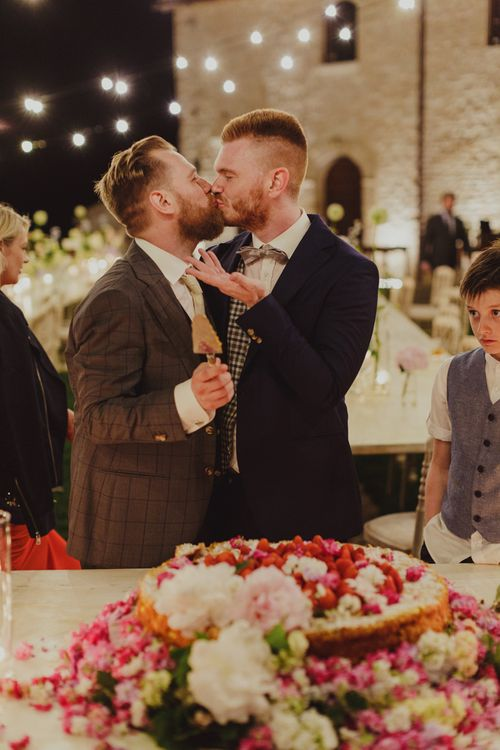 Two Grooms Cutting the Wedding Cake and Kissing