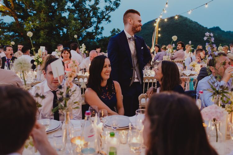 Wedding Guests at Outdoor Wedding Reception with Fairy Lights