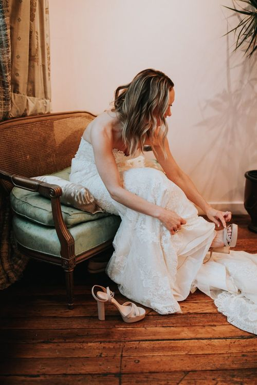Bride in Lace Pronovias Princia Wedding Dress Putting On Her Wedding Shoes