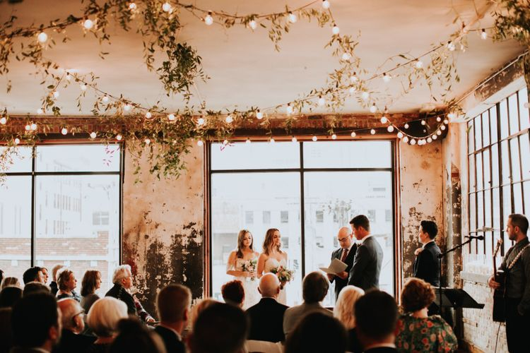 Wedding Ceremony with Hanging Festoon Lights and Greenery Wedding Decor