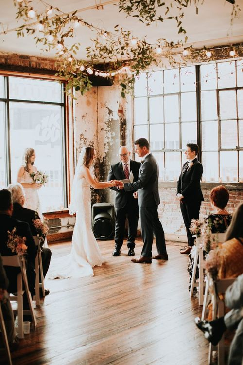 Bride and Groom Exchanging Vows at Industrial Wedding Venue with Hanging Festoon Lights and Greenery Decor