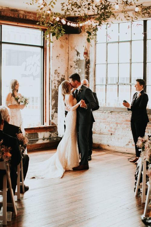 Bride in Pronovias Wedding Dress and Grooming Hugo Boss Suit Kissing at the Altar