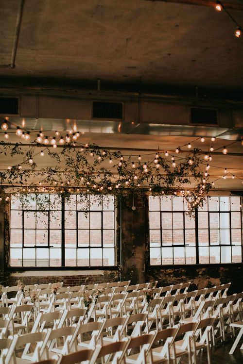 Industrial Wedding Venue with Hanging Festoon Lights and Greenery Wedding Decor