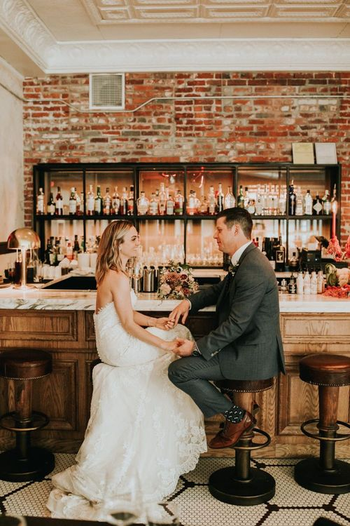 Bride and Groom Sitting at the Bar of Their Wedding Venue