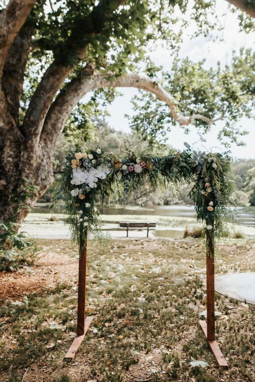 Wooden Frame Floral Arch Covered in Peach, White and Green Wedding Flowers